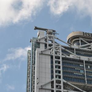 Строительные краны, которые похожи на пушки, установлены на здании HSBC